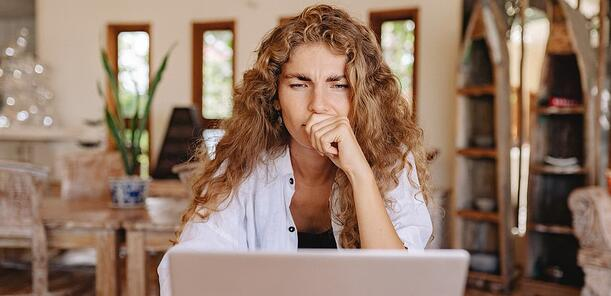 Website visitor on laptop annoyed by too many pop-ups